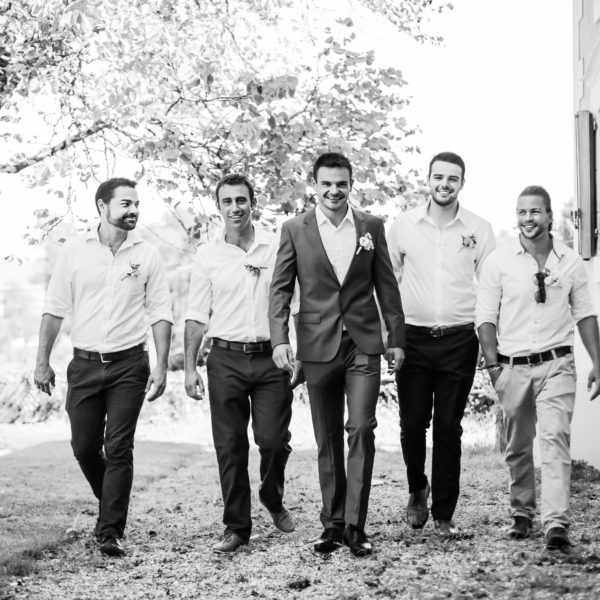 Men walking towards the camera during a wedding in France.