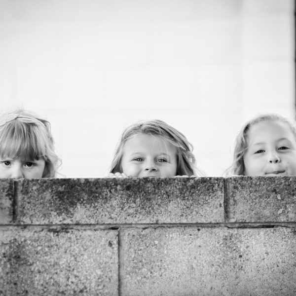 Girls looking over a wall at a wedding.
