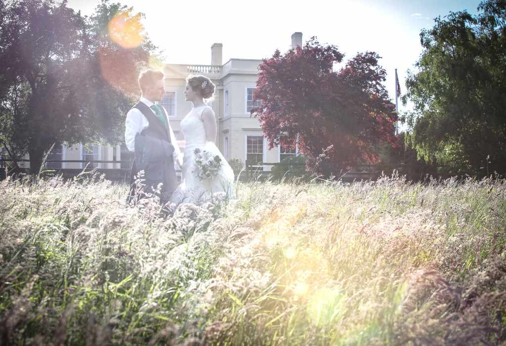 Wedding photograph of couple in long grass in a field. With sun and romance. Ramontic photograph edited with a vintage feel. Cornish wedding;