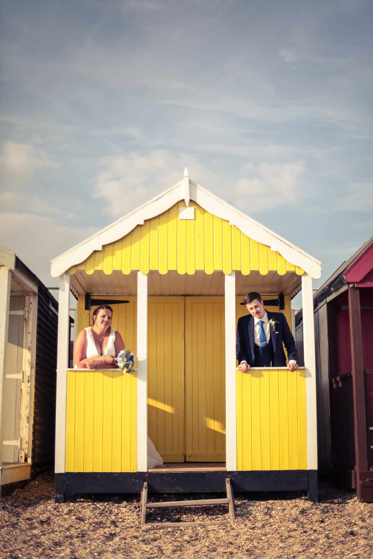 Real wedding in Essex. A couple stand in a beach hut. Wedding Photography. your perfect wedding photographer.