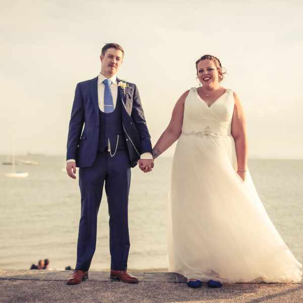 Bride and Groom holding hands at a wedding next to the sea in essex.