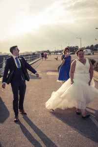 A bride and groom walking down the street after having some photos taken on a beach.