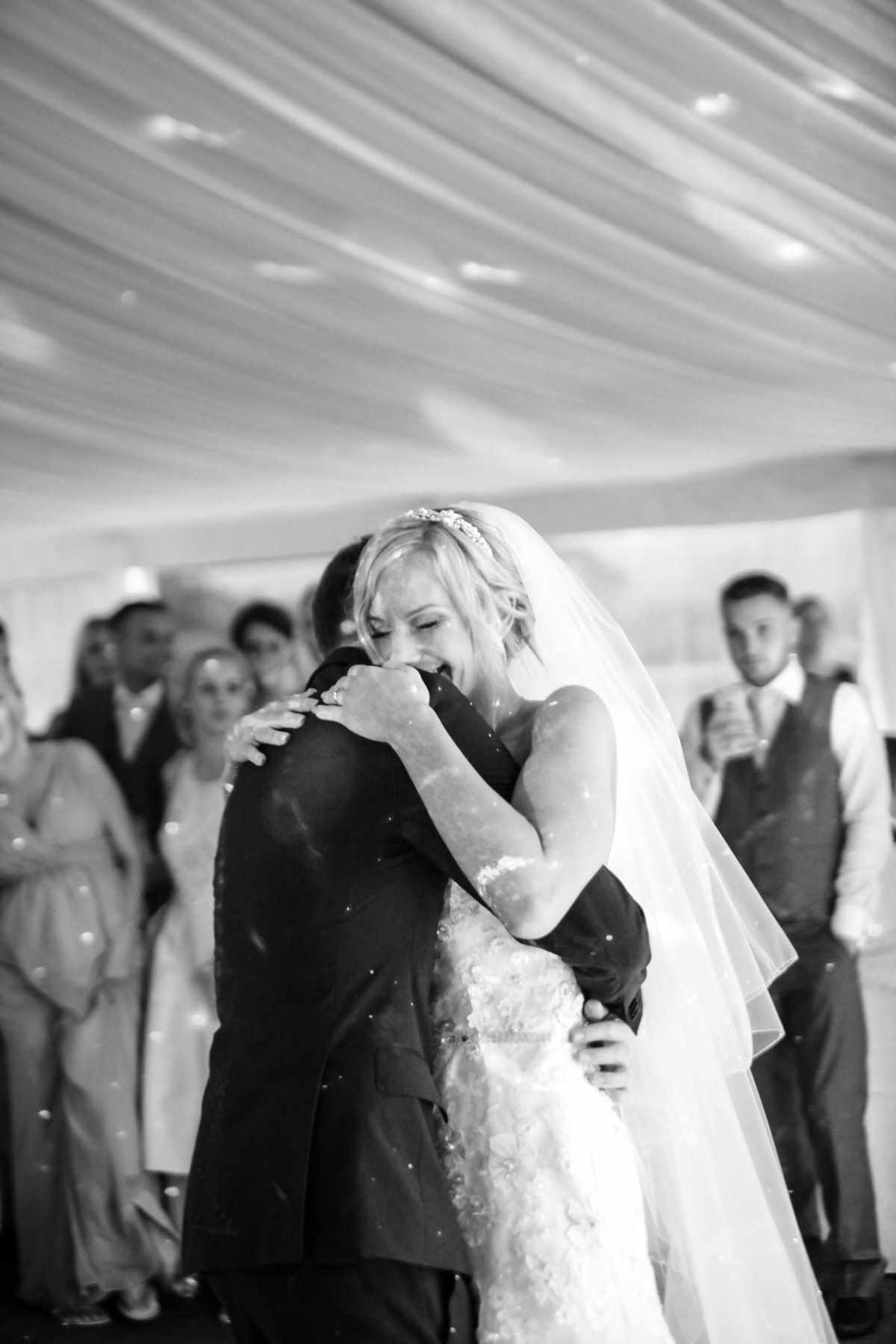 Bride holding onto her groom at her wedding whilst dancing. Romantic wedding photography.