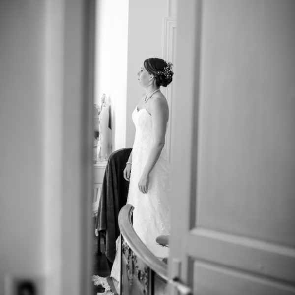 A bride looking at herself getting ready in a mirror in a french house during her wedding. Creative edit in black and white.