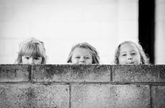 reportage wedding photographer. Girls looking over a wall at a wedding