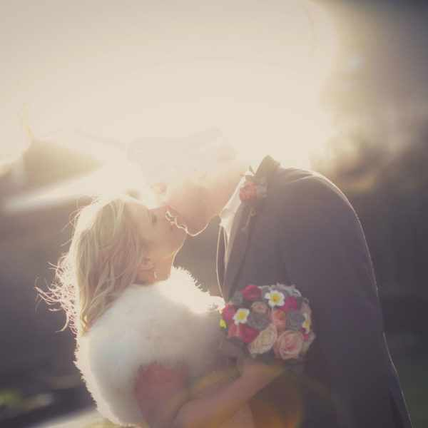 Kissing in the sun. Romantic wedding photo with vintage colours.