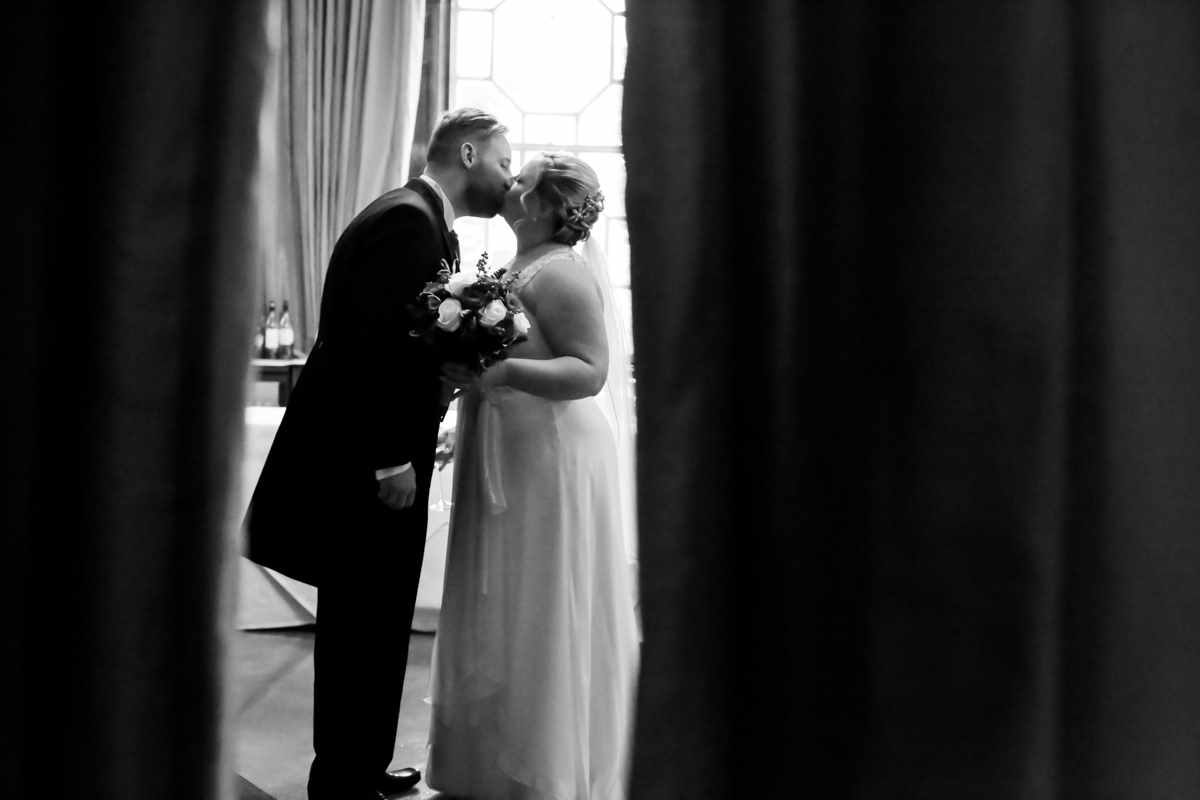 cornwall wedding photographers,Fowey Hall, Cornwall weddings, wedding photography, black and white shot of couple hidden by a curtain.