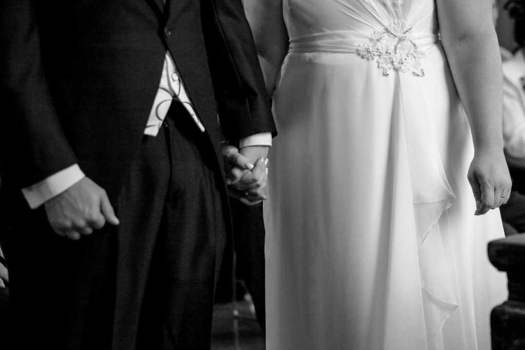 The bride and groom holding hands at a wedding by a Cornwall wedding photographer