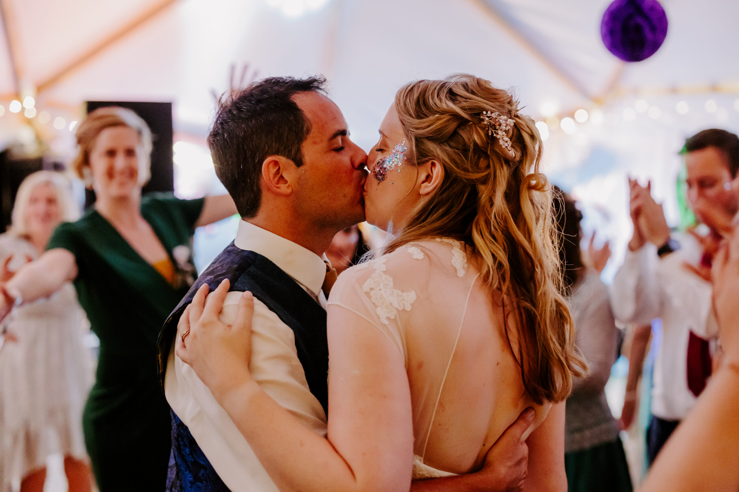 couple kiss at marquee wedding
